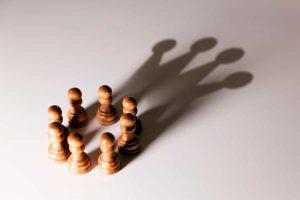 Imagem com diversas peças de Xadrez com uma sombra formando uma coroa