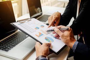 Pessoa segurando uma prancheta com gráficos, analisando os resultados da estratégia de Marketing de Conteúdo.